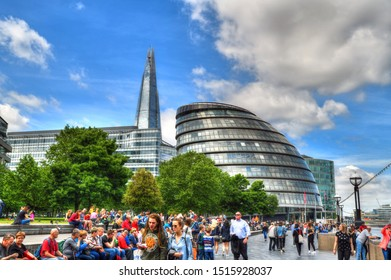 LONDON, UK, MAY 31: Colorful HDR image of tourists walking at a promenade near the new City Hall of London on clue cloudy sky. London, UK, May 31, 2019
