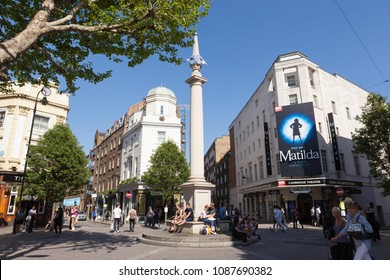 LONDON, UK - MAY 7, 2018: Tourists resting in the centre of Seven Dials in Covent Garden on a sunny day.