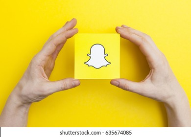 LONDON, UK - May 7th 2017: Hands holding Snapchat logo. Snapchat is a popular social media application for sharing messages,  images and videos