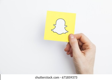 LONDON, UK - May 7th 2017: Hand holding Snapchat logo. Snapchat is a popular social media application for sharing messages, images and videos