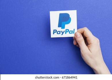 LONDON, UK - May 7th 2017: Hand holding Paypal logo. Paypal is an internet based digital money transfer service