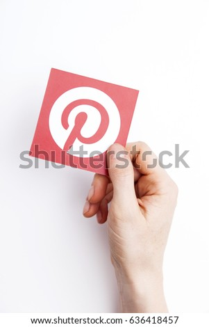 LONDON, UK - May 7th 2017: Hands holding Pinterest logo. Pinterest is a popular social media application for sharing images