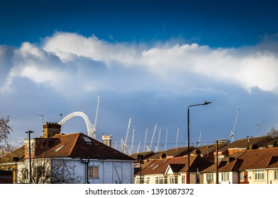 London U.K. Neasden,nr Wembley,circa February 2019 Looking towards Wembley showing Housing rooftops with construction cranes and the edge of wembley stadium in a dramatic light