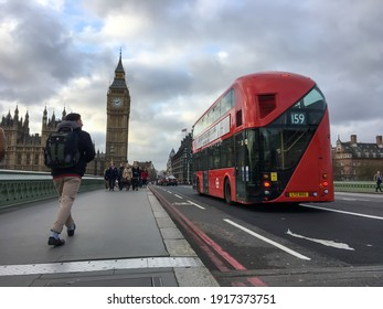 London, UK - Nov 2016: Scene at Westminster Bridge pedestrian with people and red double decker bus on road. Big Ben and Westminster palace in background.