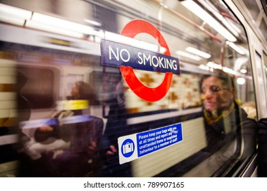 LONDON, UK - NOVEMBER 03, 2012:  passengers reflecting in a London Underground carriage window with No Smoking sign on it