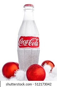 LONDON, UK - NOVEMBER 07, 2016: Classic bottle Of Coca-Cola on white background with christmas toys and snow