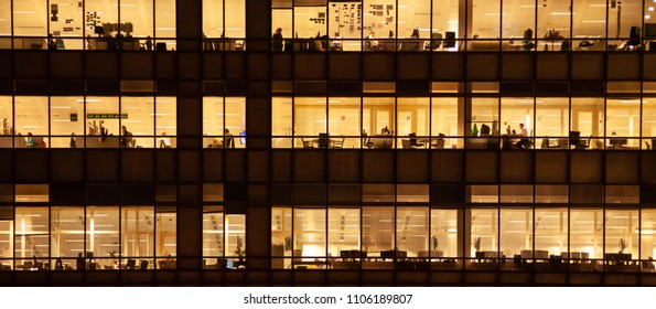 London, UK -  November 1, 2013: panoramic view of a window with people working in the interior of an office building at night.