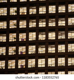 London, UK -  November 1, 2013: squared image of a window with people working in the interior of an office building at night.