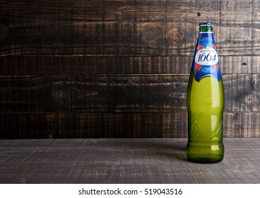 LONDON, UK- NOVEMBER 15 ,2016. Cold bottle of Kronenbourg 1664 beer on wooden background. A 5.5% pale lager is the main brand of Kronenbourg Brewery owned by the Carlsberg Group