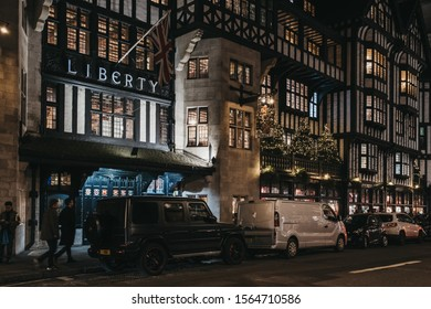London, UK - November 17, 2019: Facade of Liberty Department Store with Christmas trees in Oxford Circus, at night. Opened in 1875 it is famous for luxury goods and classic Liberty designs.