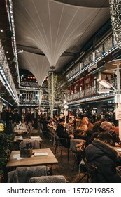 London, UK - November 17, 2019: People sitting at the tables inside Kingly Court decorated with Christmas lights, a three-storey alfresco food and dining courtyard in the heart of Londons West End.