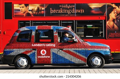 LONDON, UK - NOVEMBER 18, 2011: Old taxi tuned with Union Jack flag against traditional double-decked red bus on London streets