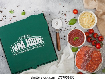 LONDON, UK - NOVEMBER 20, 2019: Box of Papa John's pepperoni pizza with salami, cheese and tomatoes on light background.