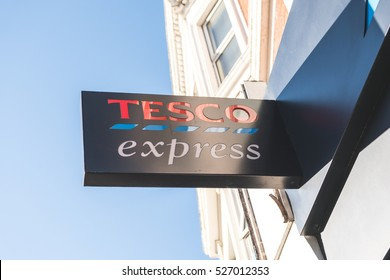 London, UK - November 2016: Tesco supermarket logo on top of store exterior against a blue sky and victorian house