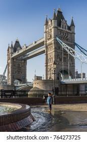 London, UK - November 22, 2017:   Juxtaposition of Eastern Asian boy near Tower Bridge in London - Victorian engineering on the river Thames