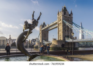 London, UK - November 22nd, 2017: Juxtaposition of David Wynne's Girl With A Dolphin Statue near Tower Bridge in London - Victorian engineering on the river Thames