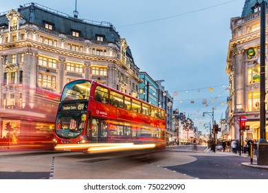 LONDON, UK - NOVEMBER 23, 2015:  Oxford Circus with a red Double Decker bus and traffic light trails. Crowd on pavement during Christmas time in London