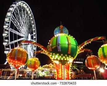 LONDON, UK – NOVEMBER 27, 2012: Winter Wonderland Christmas market in Hyde Park, London, England. Ferris wheel and colorful illuminated ride on dark winter night.