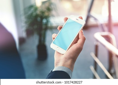 LONDON, UK, NOVEMBER 27, 2017 Businessman holding smartphone in hand. Clipping path included