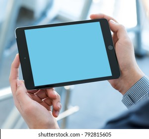 LONDON, UK, NOVEMBER 27, 2017 Businessman holding tablet pc device in hands. Clipping path included