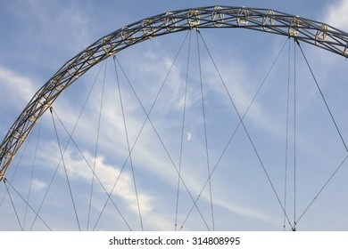 LONDON, UK - NOVEMBER 28: The architecturally striking arch of the Wembley stadium with a moon and cirrus clouds in the background on November 28, 2014 in London / Wembley bow