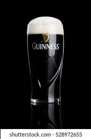 LONDON, UK - NOVEMBER 29, 2016: Glass of Guinness original beer on black background. Guinness beer has been produced since 1759 in Dublin, Ireland.