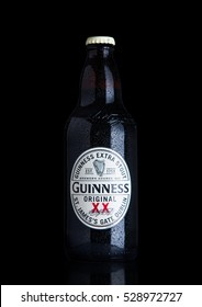 LONDON, UK - NOVEMBER 29, 2016: Guinness extra stout beer  bottle on black background. Guinness beer has been produced since 1759 in Dublin, Ireland.