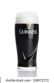 LONDON, UK - NOVEMBER 29, 2016: Glass of Guinness original beer on white background. Guinness beer has been produced since 1759 in Dublin, Ireland.
