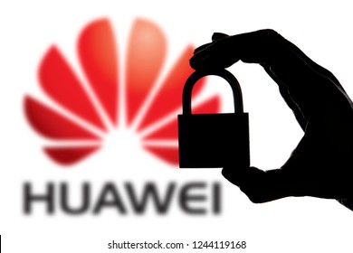 LONDON, UK - November 29th 2018: Huawei security issues. Silhouette of a hand holding a padlock in front of the Huawei logo.