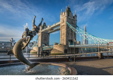LONDON, UK - NOVEMBER 4, 2014 : Sculpture of a girl and dolphin by sculptor David Wynne on the north bank of the River Thames in front of Tower Bridge in central London.