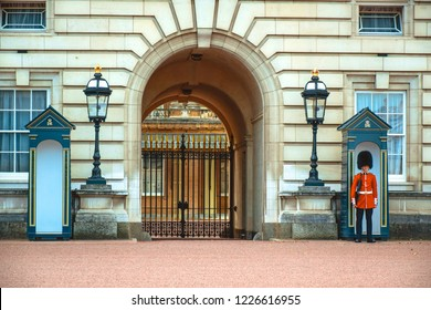 LONDON, UK - OCTOBER 13: Armed royal grenadier guard standing his position at a sentry post in front of Buckingham Palace, also known as Buckingham House, located in the city of Westminster, Uni