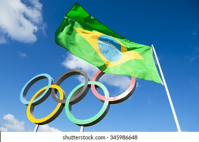 LONDON, UK - OCTOBER 14, 2015: Brazilian flag flies next to the Olympic rings standing under bright blue sky in the Queen Elizabeth Olympic Park. [illustrative editorial]