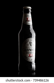 LONDON, UK - OCTOBER 15, 2017: Guinness extra stout beer bottle on black background. Guinness beer has been produced since 1759 in Dublin, Ireland.