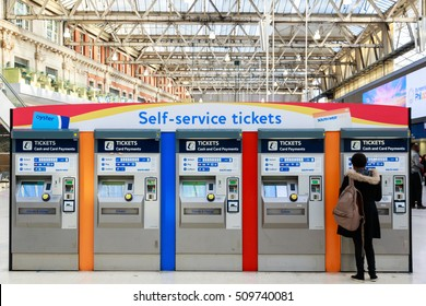 London, UK - October 18, 2016 - A commuter purchasing tickets from self-service tickets machines at Waterloo train station