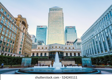 London, UK - October 20, 2016 - People hanging around Cabot Square in Canary Wharf with illuminated One Canada Square building in the background