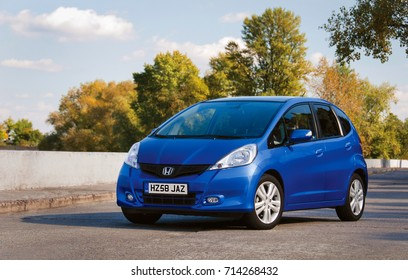 LONDON, UK - OCTOBER 20, 2016: Blue car Honda Jazz parked on the road against the background of the autumn forest. Automotive photography. Space for text. Background with car. Private city Car Honda.