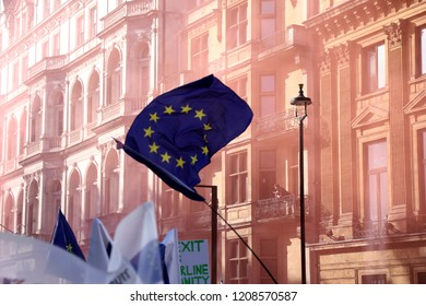 London, UK – October 20 2018: A European Union flag is waved above the crowd on Piccadilly, during an anti-Brexit march through central London, with the air turned pink from flares