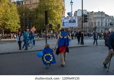 London, UK - October 20, 2018 - Man and boy wearing EU flag on their backs walk in Trafalgar Square at the People's Vote march
