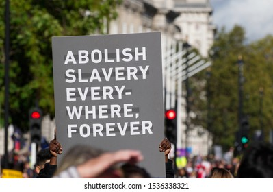 """London, UK. October 20 2019. A Walk for Freedom protestor with a sign that reads """"Abolish Slavery Everywhere Forever"""" Walk For Freedom  is a global fundraising and awareness event."""