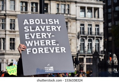 "London, UK. October 20 2019. A Walk for Freedom protestor with a sign that reads ""Abolish Slavery Everywhere Forever"" Walk For Freedom  is a global fundraising and awareness event."