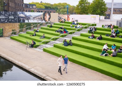 London, UK - October 2017: Young People students sitting outdoor on Granary Square steps. Granary Square is a public square on the banks of Regent's Canal in the heart of King's Cross, London, UK