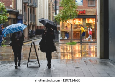 London, UK - October, 2018. Young girls walking with umbrellas under the rain in Shoreditch.
