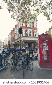 LONDON, UK - October 2019: London cityscape. Bicycles parking and telephone booth, London, UK