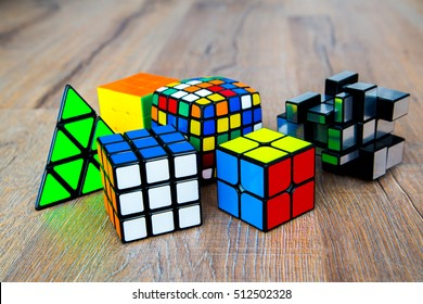 London, UK - October 20th, 2016: Colorful several Rubik's cubes 2x2 and 3x3, 5x5 and pyramid on wooden background