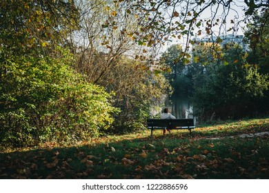 London, UK - October 27, 2018: Person sitting on a bench, relaxing by the pond in Hampstead Heath. Hampstead Heath covers 320 hectares one of London's most popular open spaces.