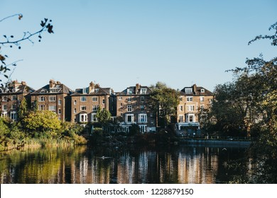London, UK - October 27, 2018: Row of semi-detached houses in Hampstead, facing a pond in Hampstead Heath. Hampstead Heath covers 320 hectares one of London's most popular open spaces.