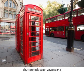 LONDON, UK - OCTOBER 7, 2014:  London England street scene featuring iconic red phone box and double-deck bus in background.