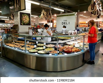 London, UK, October 8th 2018: A shop worker behind the deli counter preparing assortment of fresh meat and vegetables, whilst a customer looks on