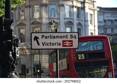London, UK, Parliament Sq and Victoria station sign with Red Bus No 23 at Trafalgar Square