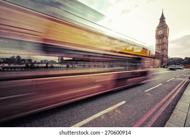 London, the UK. Red bus in motion and Big Ben, the Palace of Westminster